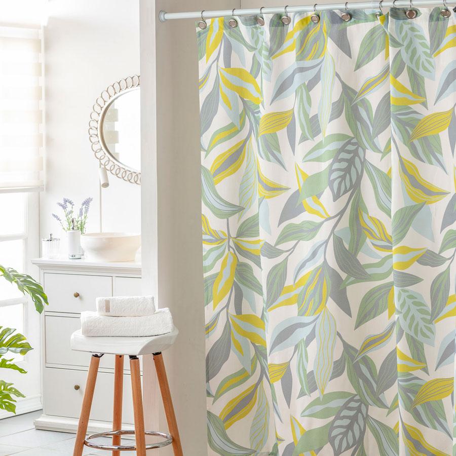 baño con cortina estampada con hojas verdes y amarillas