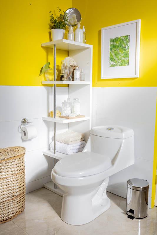 Baño amarillo con repisa con objetos decorativos