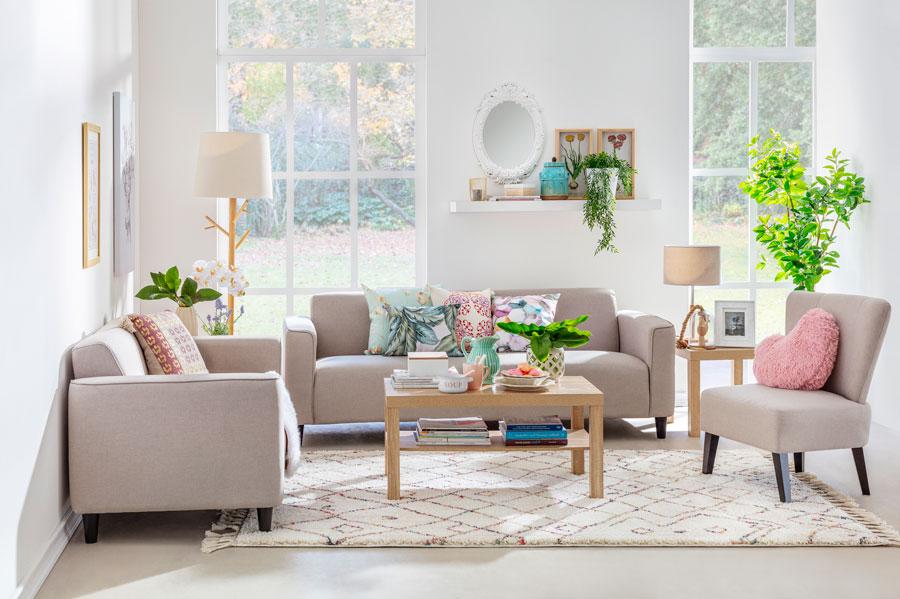 Living con paredes blancas, sofas en tonos beiges y cojines en verde y rosado