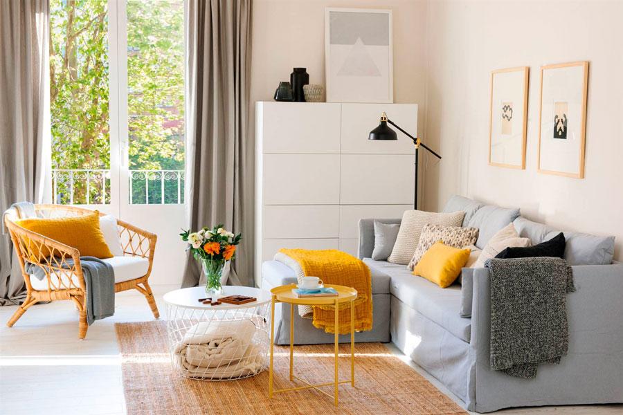 Living con paredes blancas, sofas en grises y detalles en tonos mostaza