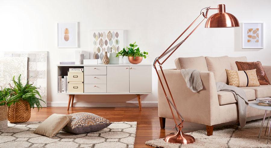 Sala de estar, con dos alfombras geométricas, una lámpara de pie flexible de cobre, un sofá de tres cuerpos con cojines decorativos y una manta, un buffet contra el muro, varios cestos con plantas dentro y tres cuados decorativos