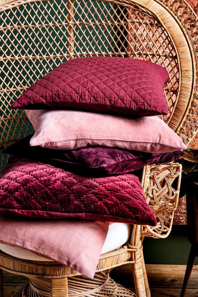 Silla de mimbre estilo pavo real, con una pila de cinco cojines en tonos burdeos y rosas encima