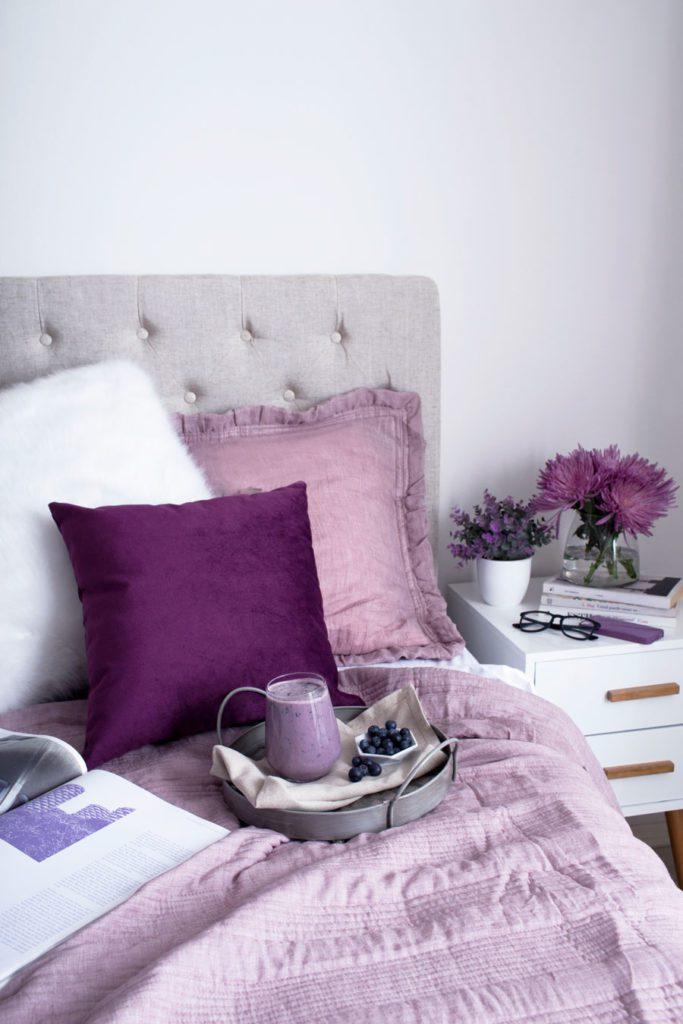 Esquina de una cama con mantas y cojines en tonos lila, con una bandeja de desayuno encima