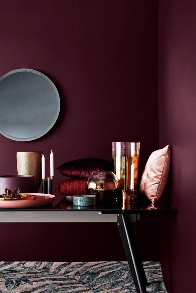 esquina con muros burdeo oscuro y una mesa de metal y vidrio, con cojines rosas, velas, bandejas y jarrones de vidrio.