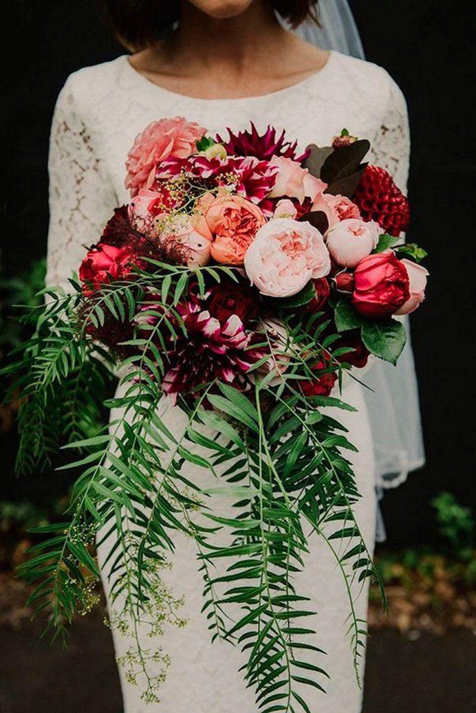 Novia posando con su ramo de flores, en tonos blanco, rosa, burdeo, lila y fucsia.