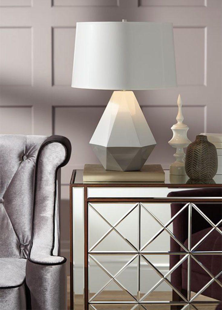 Detalle de mueble de comedor de espejos, al lado de sofá de terciopelo gris, decorado con una lámpara blanca geométrica