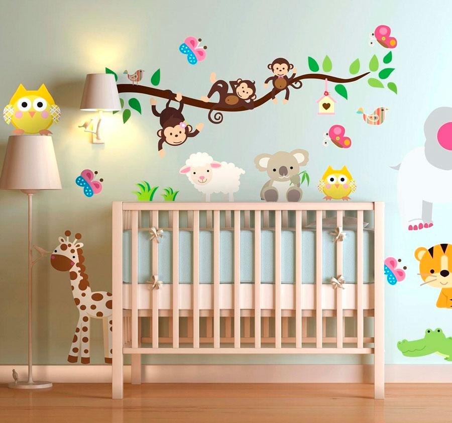Dormitorio de bebé con cuna de madera y pared llena de stickers de animales de colores.