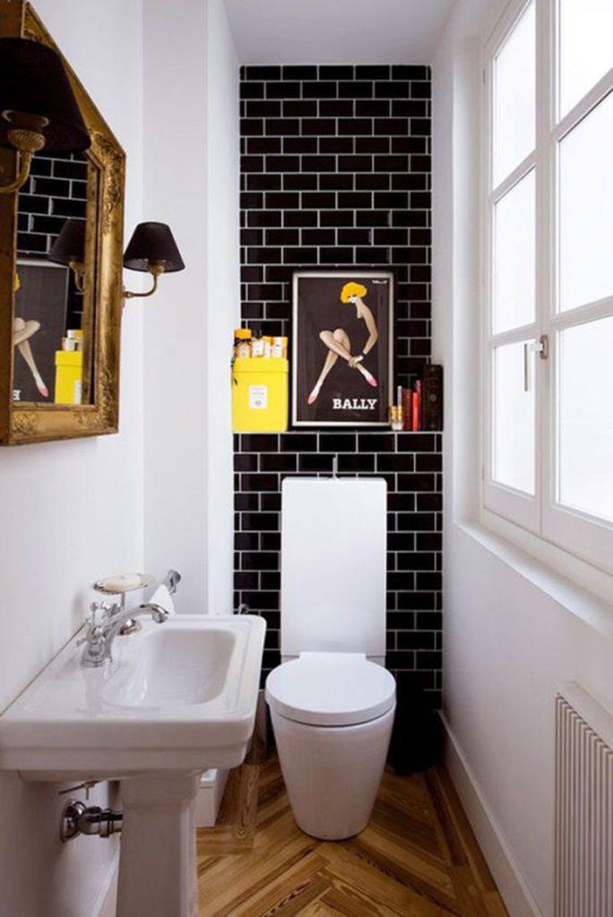 Baño de visitas angosto, con muros en blanco y uno, el más pequeño, en cerámica negra y decoración negra y amarilla.