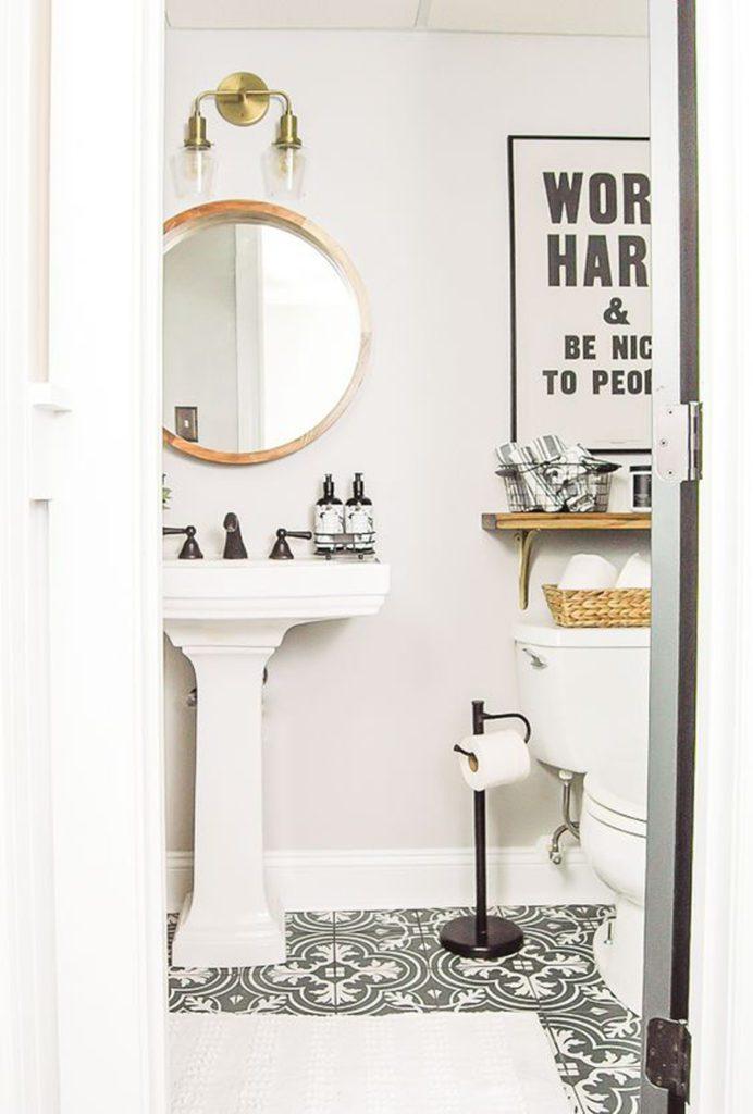 Vista de un baño desde a puerta. Decorado en blanco y con detalles metálicos y de madera. Con cerámicos decorados en el piso.