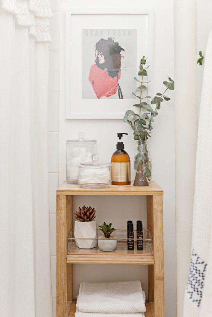 Baño pequeño, se ve una cortina de baño y un pequeño mueble de madera. Se decora con un cuadro, floreros, maceteros y frascos.
