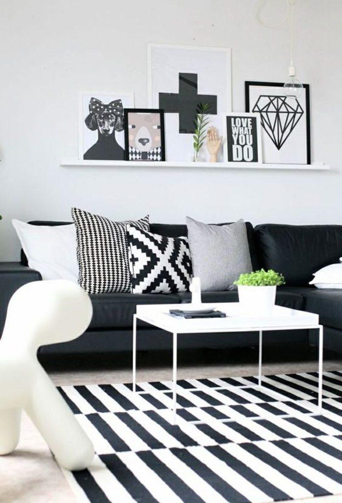 Living en blanco y negro, con alfombra y cojines decorativos con motivos geométricos