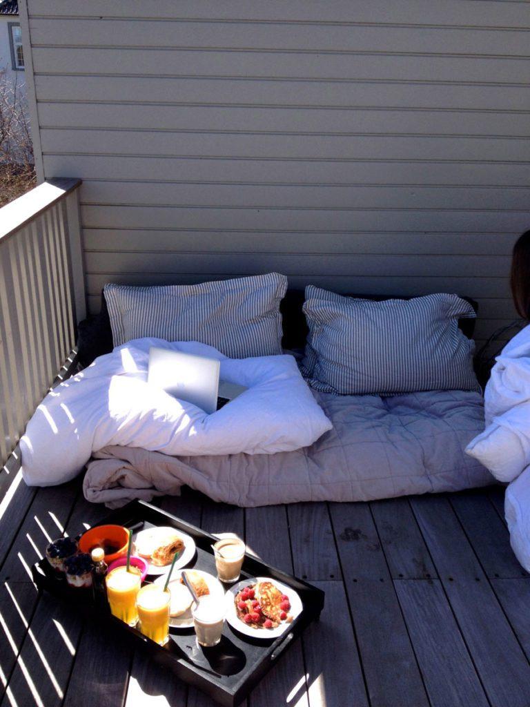 Balcón de madera con cojines en el piso y una bandeja de desayuno