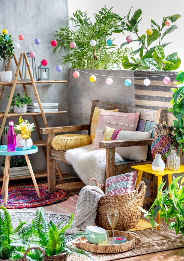 Balcón pequeño con banco de madera, cojines decorativos, alfombras, canastas y bandeja con vasos