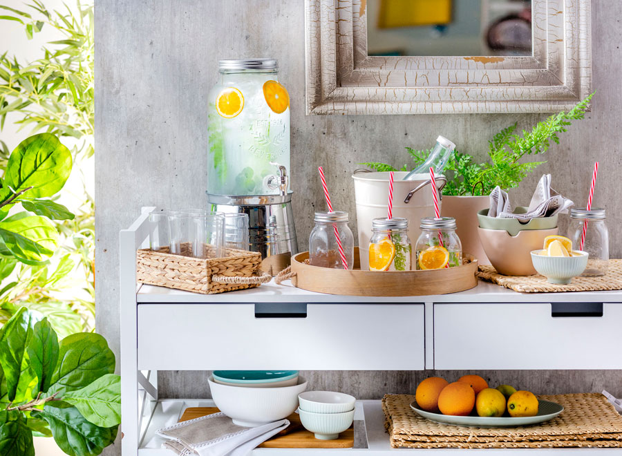 Mueble estilo buffet con bandejas de madera y mimbre, con vasos y jarros, un dispensador de agua y bowls.