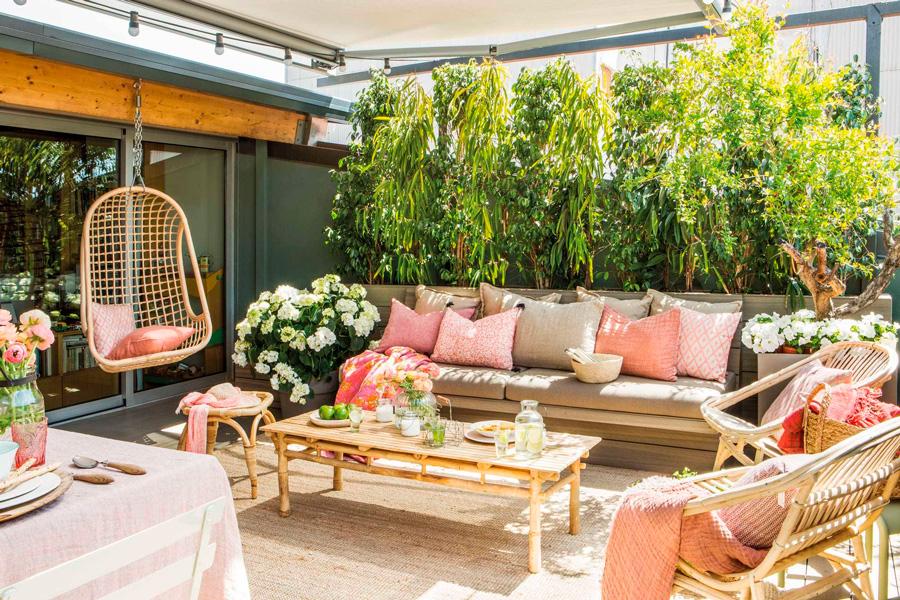 Terraza con sillones de mimbre y hamaca colgante decorado con cojines y mantas en tonos rosados