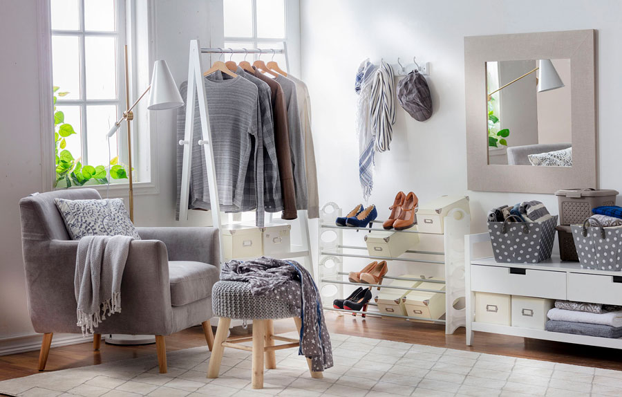 Espacio en dormitorio con zapateros, colgadores y espejo para organizar la ropa