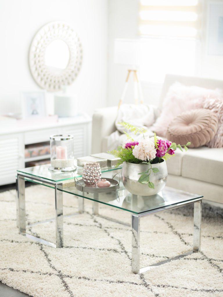 Living en color beige, mesa de centro con cubierta de vidrio y patas de metal, alfombra y sofá en tonos claros que combinan con un espejo redondo en la pared.