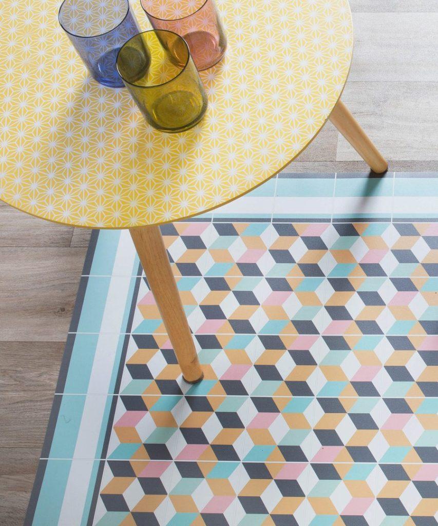 Alfombra vinílica con colores naranjo, azul, blanco y verde agua que forman un rubik. Acompañada de una mesa lateral de madera con cubierta color amarillo.