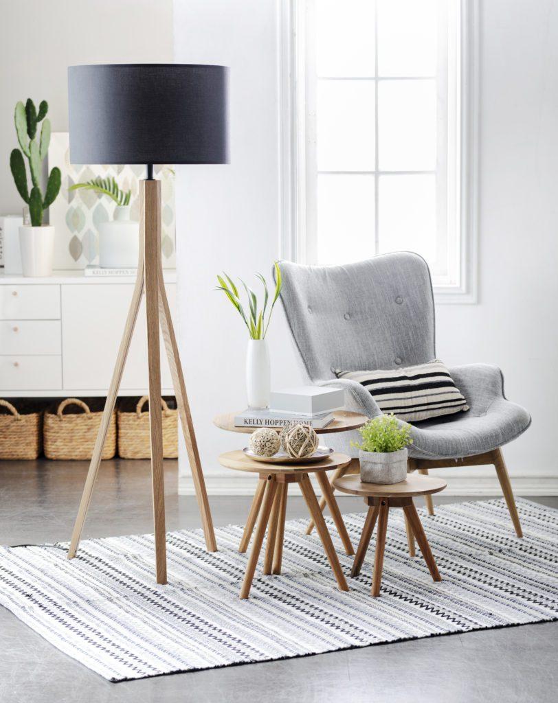 Rincón para leer, donde resalta una lámpara de pie con soporte de madera y pantalla negra, un sofá gris y juego de tres mesas de centro con adornos. Ambiente relajado y que ocupa poco espacio.