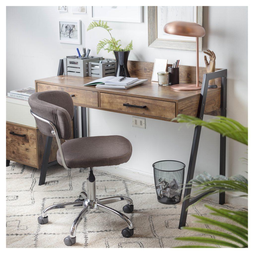 Espacio para estudiar o crear proyecto, compuesto por un escritorio de color madera, accesorios de escritorio, lámpara metálica color bronce y una silla en tonos tierra.