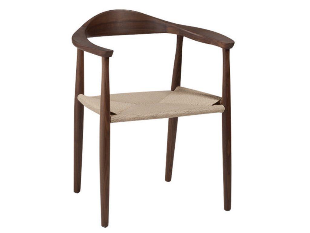 Silla de madera, café oscura, con apoya brazos y tapiz de ratán en color beige.