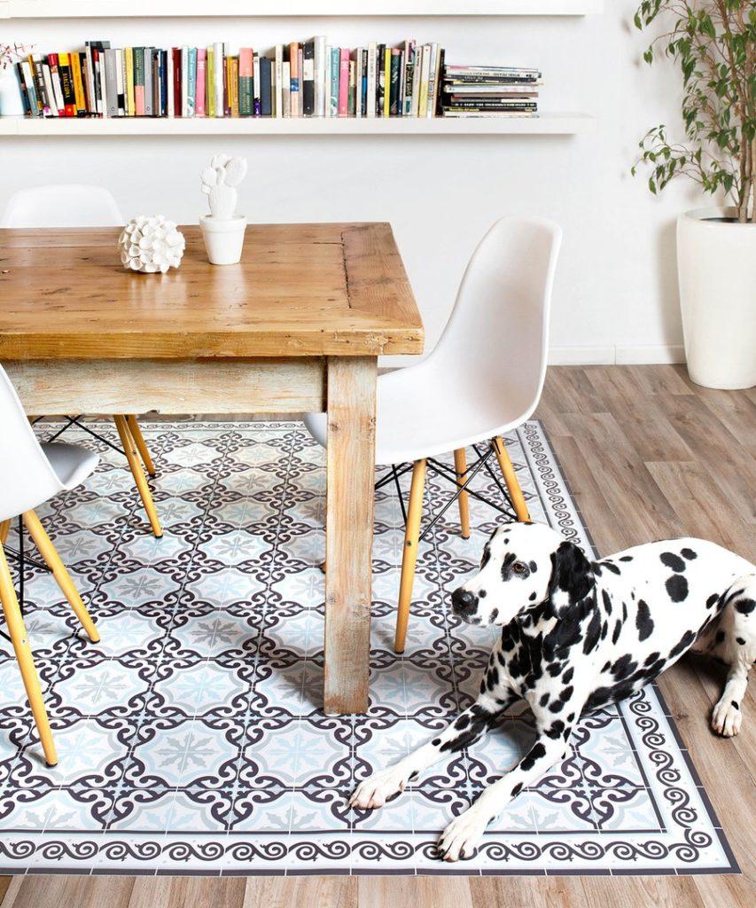 Alfombra vinílica con figuras decorativas en tonos grises. Ubicada en el suelo de un comedor de madera con sillas blancas estilo eames.