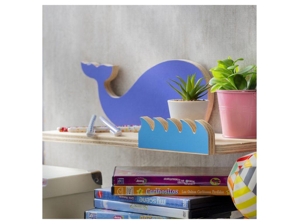 Repisa en forma de ballena de color azul en una ambiente de pieza infantil. Plantas y libros la adornan.
