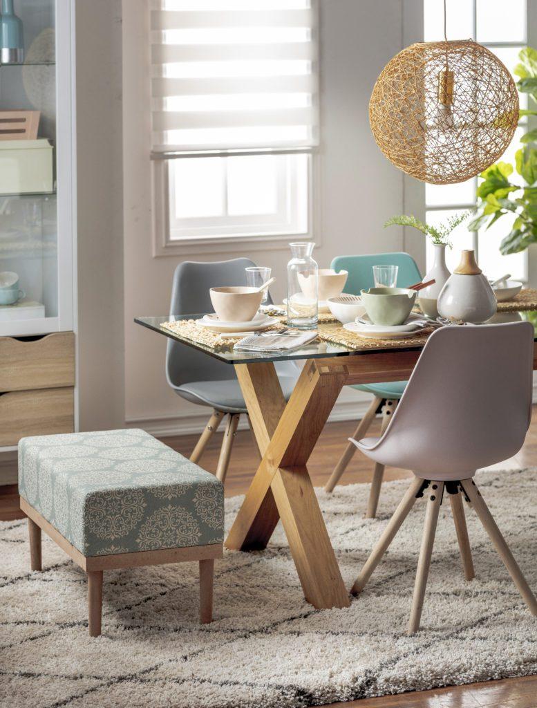 Banqueta color azul petróleo, con patas de madera y diseño marroquí en color blanco, utilizada en un comedor con la funcionalidad de una silla.