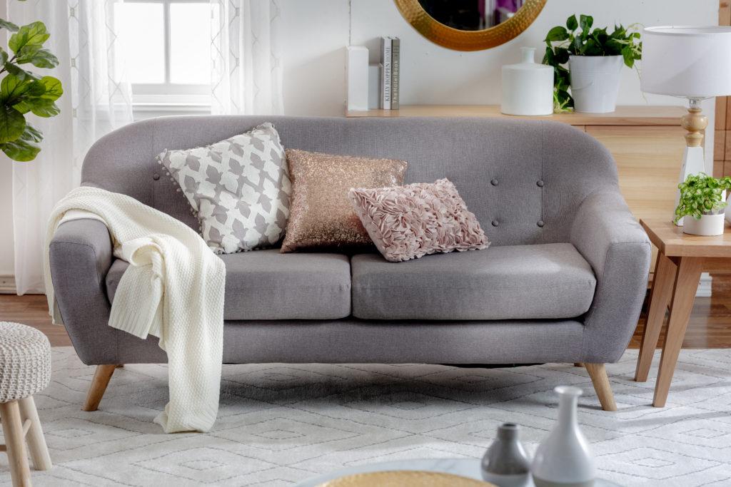 Sofá color gris con tres cojines, una manta blanca y muebles laterales de madera. Pouff y plantas alrededor.