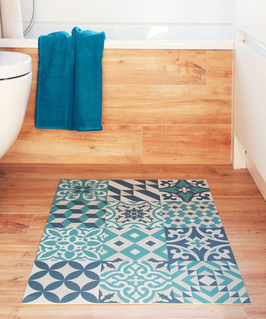 Alfombra vinílica con figuras geométricas en tonos verde agua y azul, ubicada en un baño de piso de madera.