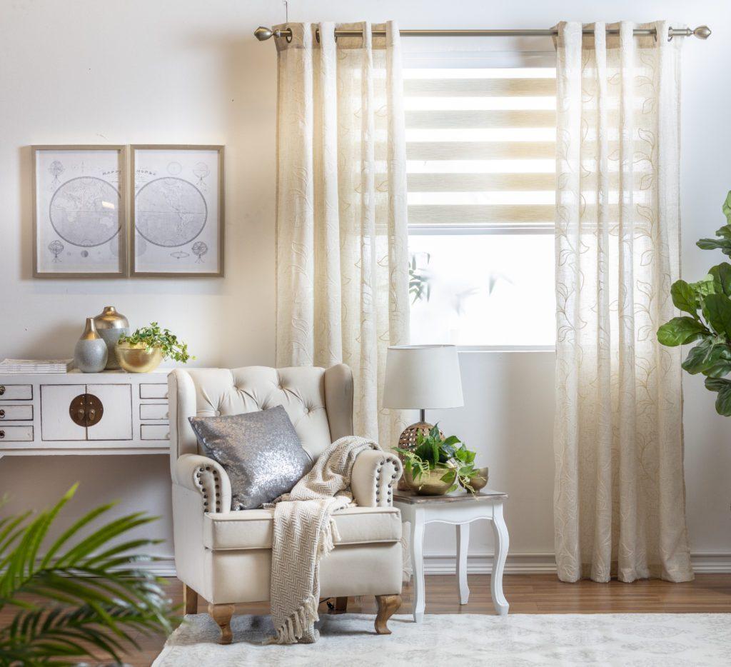 Ambiente relajado en tonos claros para hacer ver mas grande el espacio. Un sofá beige y cortinas de tela en el mismo color. Mesa lateral blanca con una lámpara. Decoración con plantas y cuadros con marcos de madera.