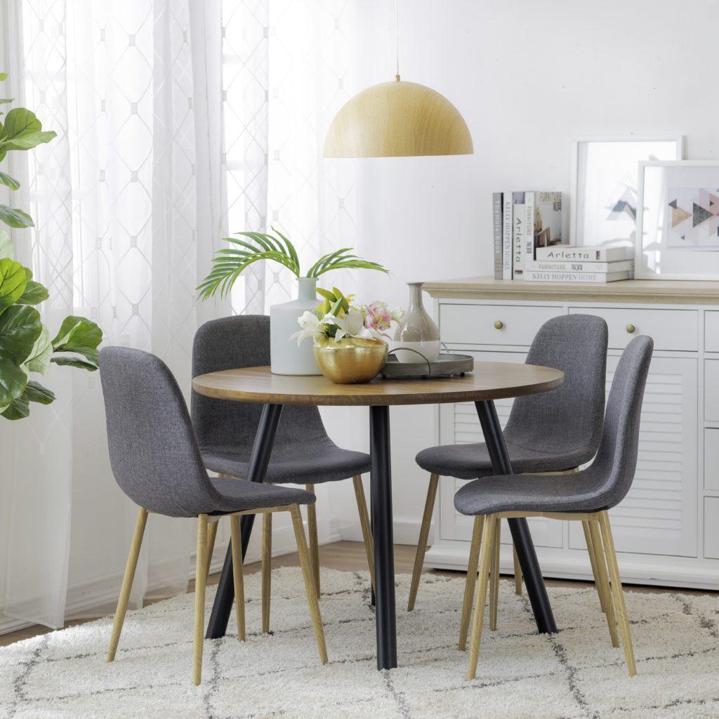 Comedor para espacios pequeños de cuatro sillas. Mesa redonda con cubierta de madera y patas de metal.