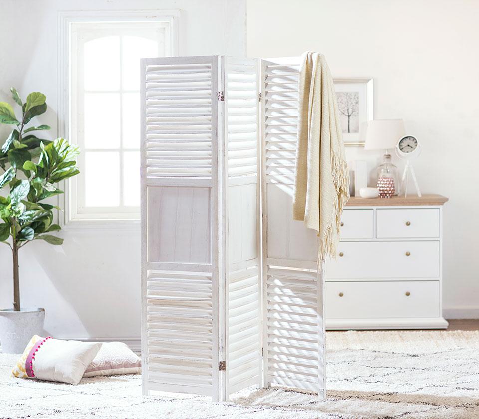 Separador de ambiente de madera, color blanco y de tres paños. Ambientado en una espacio con tonos claros.