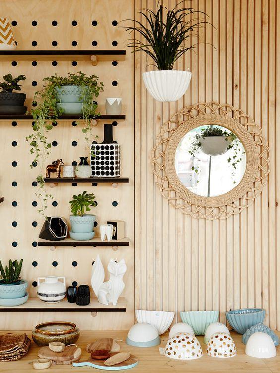Repisa de panel perforado con varias repisas que contienen adornos, plantas y otros accesorios.