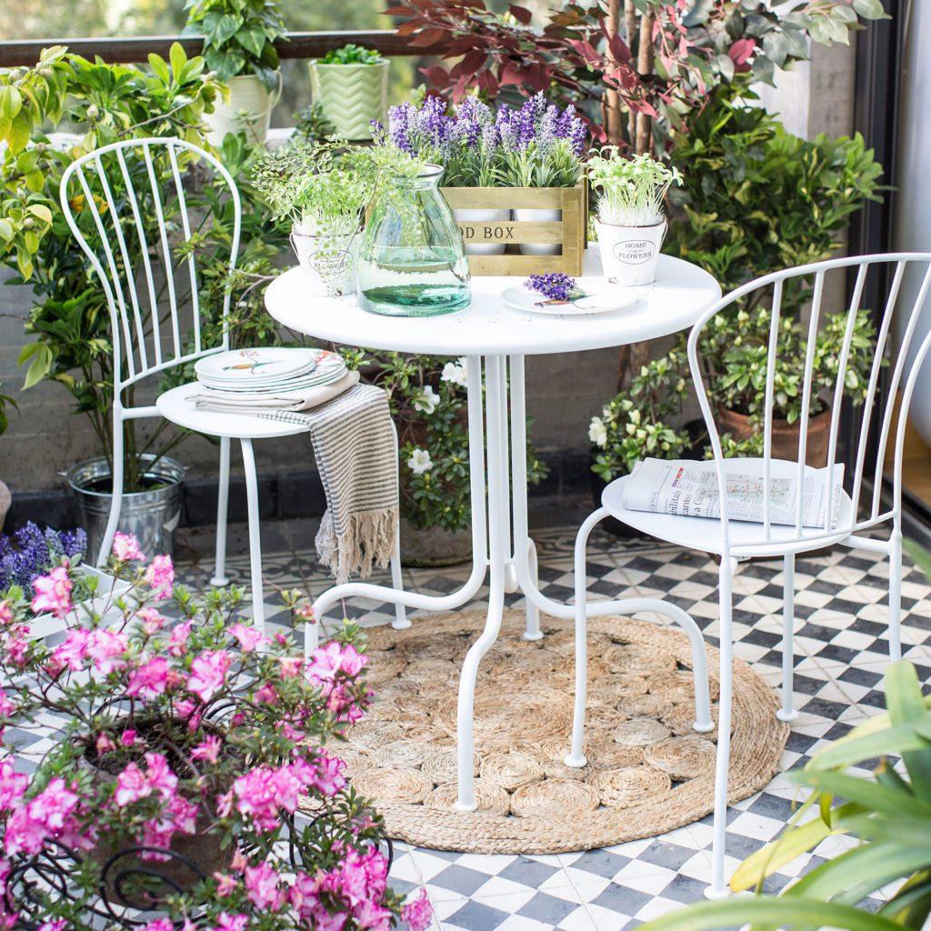 Juego de terraza con dos 2 sillas de metal y color blanco. Ambiente de balcón rodeado de flores.