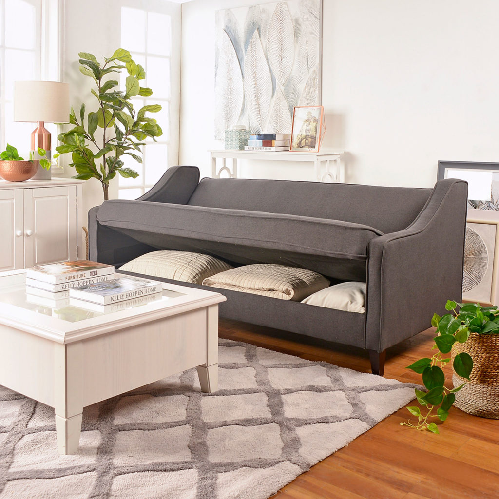 Ambiente de living con un futón color gris. alfombra y muebles en tonos claros que combinan perfectamente. El futón tiene un compartimiento extra para guarda cojines.