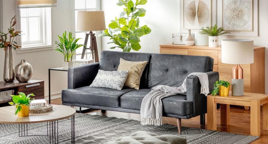 Ambiente de living con futón en color gris, alfombra en el mismo tono junto a cojines. Paredes y adornos de madera y plantas de interior alrededor.