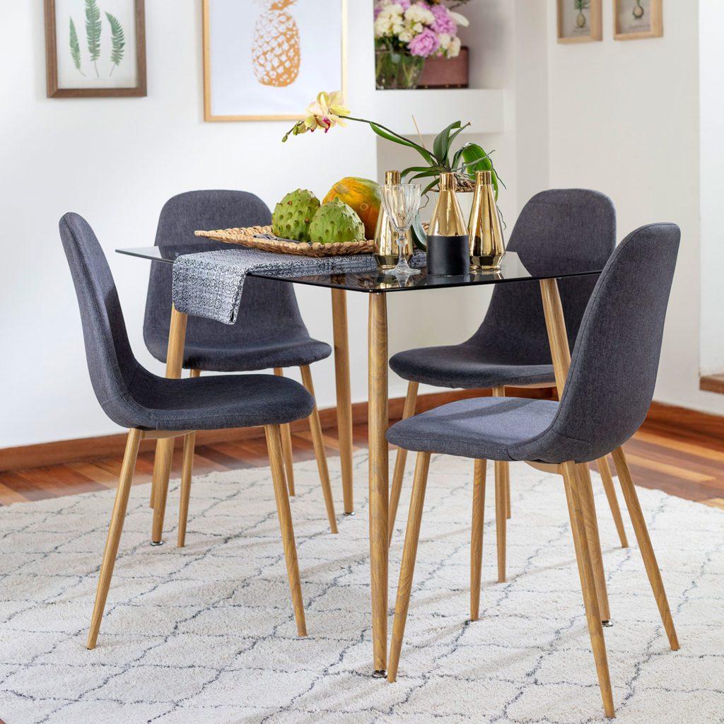 Comedor de cuatro sillas, con mesa con cubierta de vidrio y sillas con tela gris y patas de madera