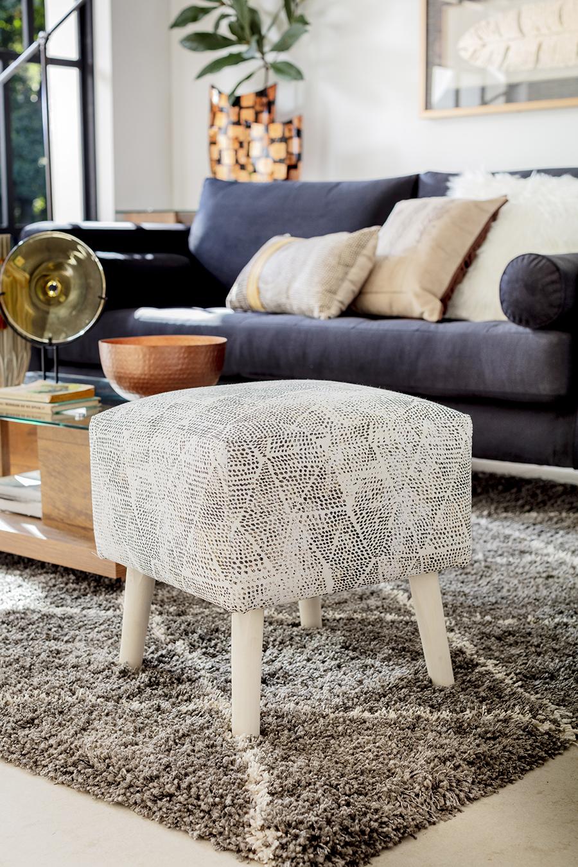 Pouf color beige con textura y patas de madera