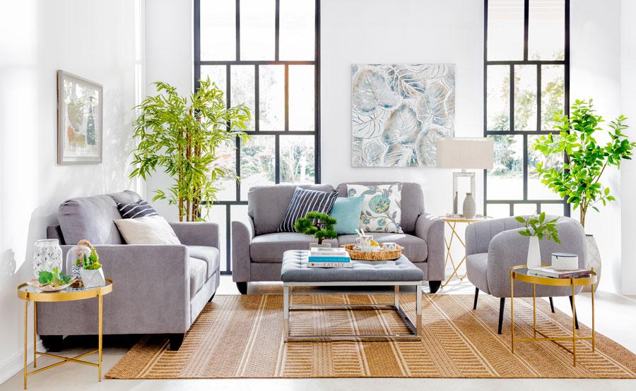 Living con alfombra que contiene las patas de todos los muebles y sillones
