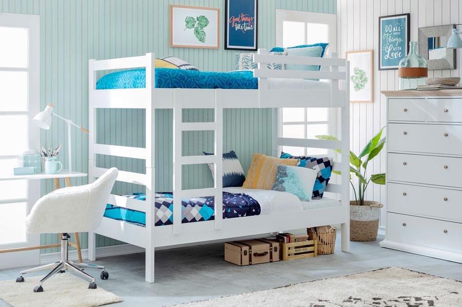 Dormitorio con cama nido blanca y ropa de cama en tonos azules