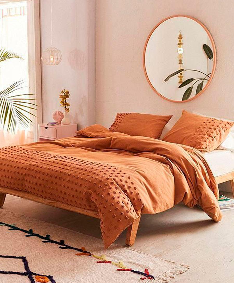 Trucos low cost: espejo redondo grande en la cabecera de cama con borden dorados.