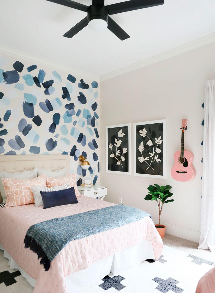 Papel mural con formas en tonalidades azules. Ubicado en el cabecero de la cama.