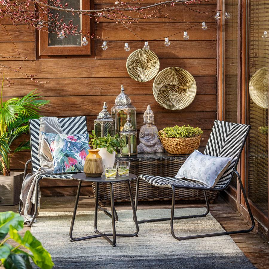 Juego de terraza a rayas en blanco y negro con dos sillas y una pequeña mesa redonda.