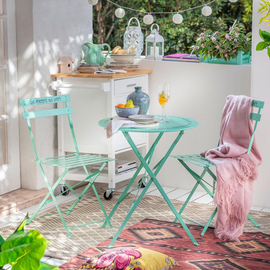 Juego de terraza de metal color calipso. Dos sillas y una mesa redonda.