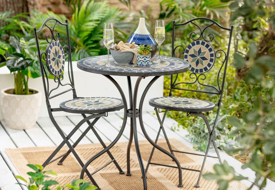 Juego de terraza de metal con diseño mosaico. Dos sillas y una mesa redonda.