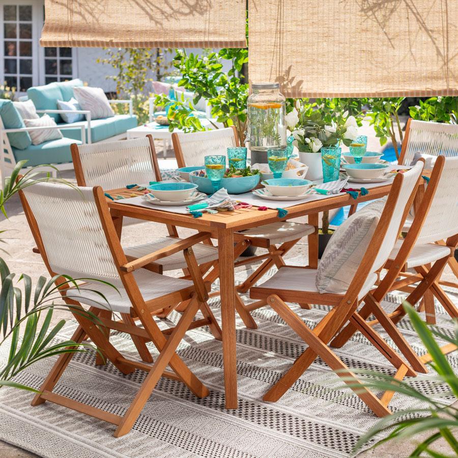 Juego de comedor de madera en terraza con con cortinas enrollables de bambú