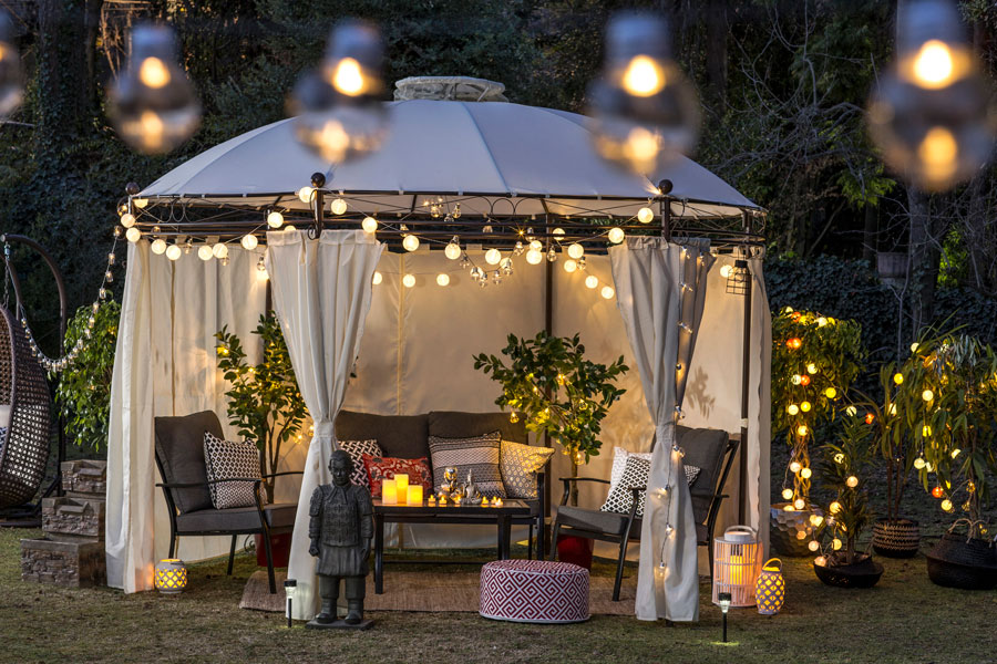 Pérgola blanca con juego de terraza iluminado con guirnaldas de luces