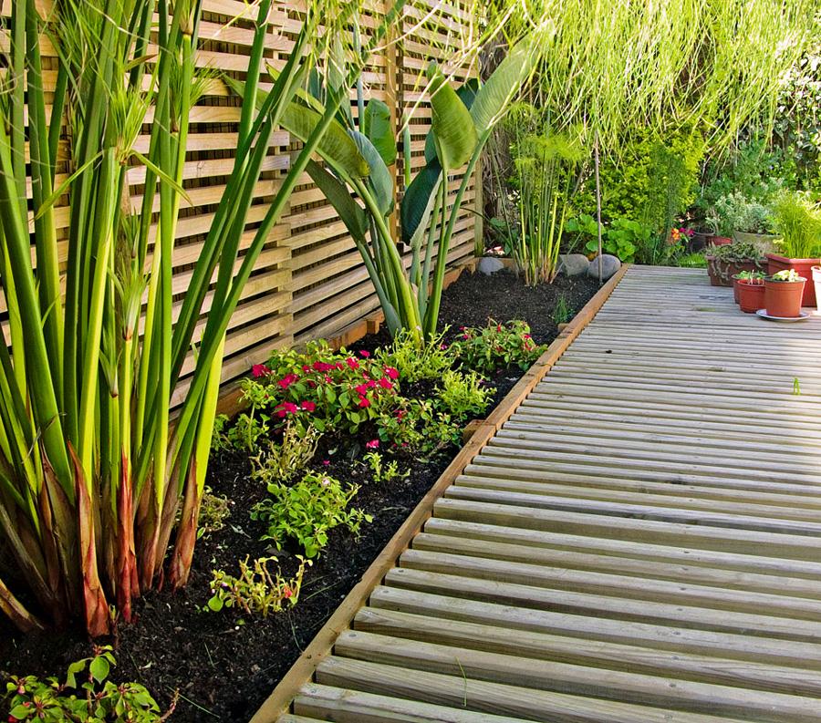 Jardinera con plantas y flores, piso de madera tipo deck