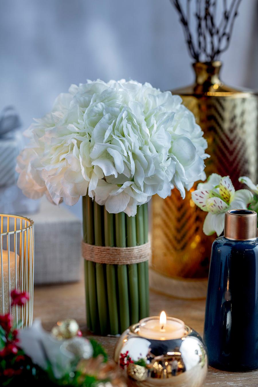 Flores blancas con vela en centro de mesa